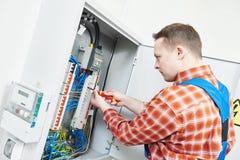 电工与在保险丝箱子的电表测试器一起使用 库存图片