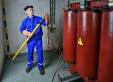 电工使用一台绝缘的棍子接地变压器 免版税库存图片