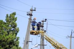 电工修理与推力的输电线 修理工作 电子接线当前修理  图库摄影