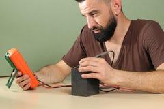 电工在实验室里检查电池 免版税图库摄影
