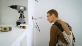 电工在白色墙壁的一个机制被隐藏的插口切开导线并且尝试在舱内甲板在修理中 股票视频