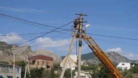 电工在高度登上导线 在高度的上升通过塔的机器 影视素材