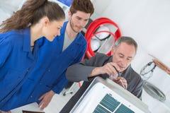 电工安装工定象空调在房子里 免版税库存照片