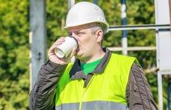 电工工程师饮料咖啡在工作场所 免版税库存图片