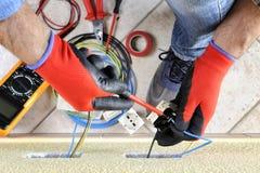 电工技术员在与在住宅电气系统的安全设备一起使用 免版税图库摄影