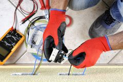 电工技术员在与在住宅电气系统的安全设备一起使用 库存图片