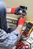 电工技术员在与在住宅电气系统的安全设备一起使用 图库摄影
