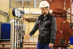 电工操作员检查和检查加热被通风的和车厢空调设备 检查测压器的HVAC工程师 免版税库存照片