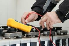 电工有黄色多用电表的检查电池 免版税库存照片
