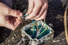电工的手有终端forbox和螺丝刀的拉紧在保险丝箱子的交换的电作动器设备 库存图片
