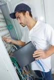 电工连接互联网服务器到电源板 库存图片