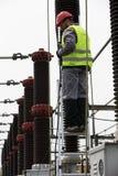 电工建造者工程师 在能源厂的电变压器 免版税库存图片