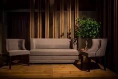 电影光 一个灰色沙发和两把灰色椅子在木腿在一个棕色木指挥台站立 免版税图库摄影
