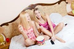 电影在家:2名可爱的可爱的相当年轻白肤金发的妇女获得坐的乐趣在床用玉米花、观看的电视和愉快的微笑 库存照片