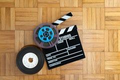 电影在木地板上的拍板和影片轴 免版税库存图片