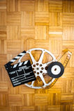电影在木地板上的拍板和影片轴 图库摄影