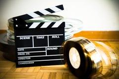 电影在木地板上的拍板和35 mm影片轴 免版税库存图片