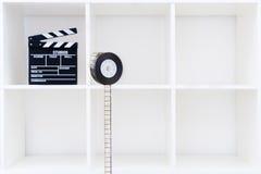 电影在白色书架的拍板和影片轴 免版税库存照片