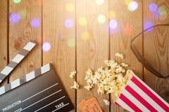电影拍板、3d玻璃和玉米花在木背景 戏院概念 免版税库存图片