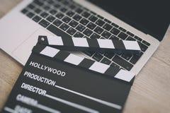 电影拍板和膝上型计算机在木头 库存照片