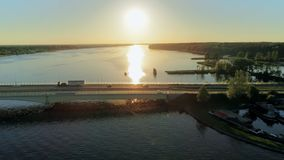 电影鸟瞰图驾车在横跨湖的桥梁在夏天日落 股票视频