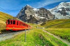 电旅游火车和艾格峰北部面孔, Bernese Oberland,瑞士 免版税库存图片