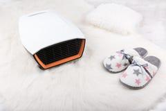 电暖气和对在白色毛茸的地毯的温暖的拖鞋 背景蓝色雪花白色冬天 免版税库存照片