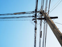 电杆和被缠结的电缆与蓝天 免版税库存图片