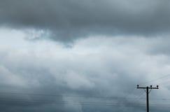 电杆和黑暗的天空 库存图片