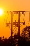 电杆输电线和导线剪影在日落 免版税库存照片