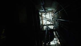 电梯在轴进来下来 在上面,您能看到推力、缆绳和蓝天的机制 股票录像