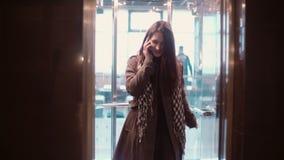 电梯门是开放的 走开的妇女站立入推力和谈话在smarphone和 影视素材