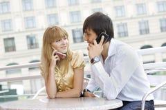 电池坐表的夫妇电话他们使用 免版税库存图片