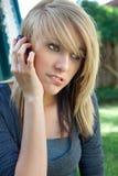 电池女孩移动电话联系少年 免版税库存图片