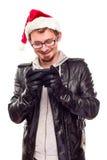 电池帽子人电话使用年轻人的圣诞老&# 免版税库存照片