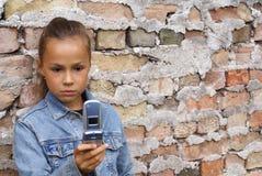 电池拨号的女孩电话 免版税库存照片