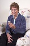 电池祖母成熟电话高级texting的妇女 免版税库存照片