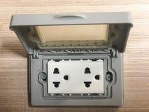 电源输出口为在木墙纸的家庭使用 免版税库存照片