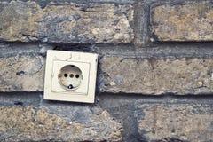 电火花塞连接器, ac出口,在砖墙上。 免版税库存照片