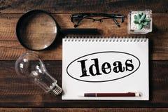 电灯泡、放大镜、玻璃、仙人掌和笔记本有想法词的在木桌上 免版税库存图片