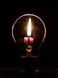电灯泡和烛光焰 图库摄影