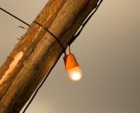 电灯泡在一根木杆烧 免版税图库摄影