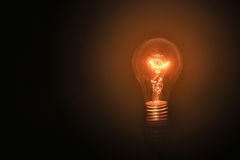 电灯泡在黑背景和没有接线打开与在想法的概念的成功的概念 点燃在顶楼样式 库存图片