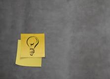 电灯泡如创造性在纹理w的被弄皱的稠粘的便条纸 库存照片