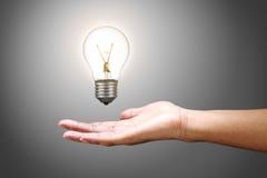 电灯泡用手 图库摄影