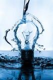 电灯泡用水飞溅了在与蓝色颜色的黑暗的表面 库存图片