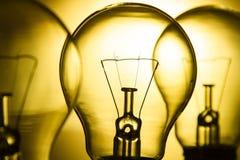 电灯泡行在明亮的黄色背景的 库存图片