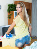 电烙与铁的白肤金发的妇女 免版税库存图片