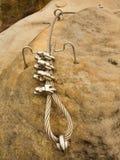 电烙在块固定的扭转的绳索由螺丝短冷期勾子 绳索末端细节停住入砂岩岩石 库存照片