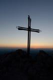 电烙在山的十字架和天的最后光芒 免版税库存照片